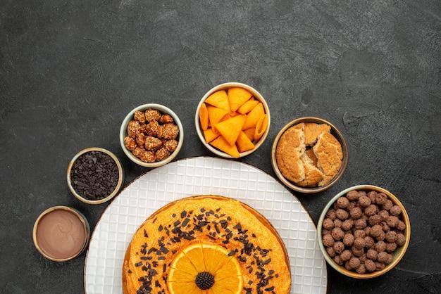Bovenaanzicht heerlijke taart met stukjes sinaasappel en vlokken op donkere bureau biscuit fruit dessert taart taart thee