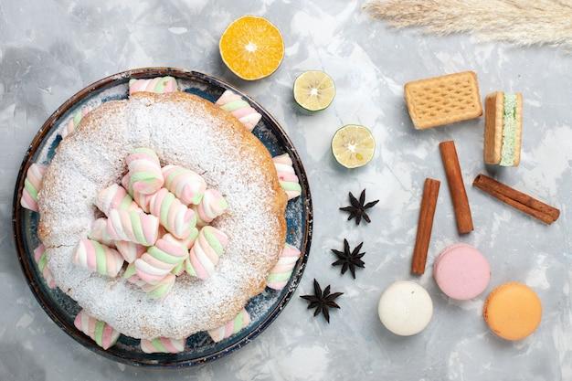 Bovenaanzicht heerlijke taart met suikerpoeder en marshmallows op wit