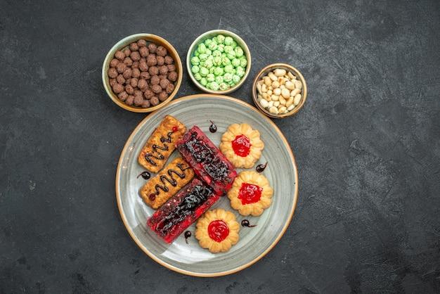 Bovenaanzicht heerlijke taarten fruitige snoepjes met koekjes en noten op de donkere achtergrond suikerkoekje biscuit cake zoete taart