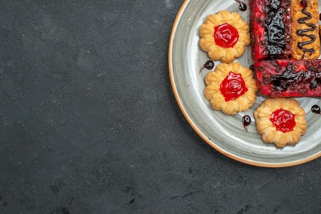 Bovenaanzicht heerlijke taarten fruitige snoepjes met koekjes op donkere achtergrond suiker thee koekje biscuit cake zoete taart