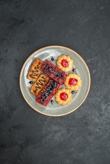 Bovenaanzicht heerlijke taarten fruitige snoepjes met koekjes op een donkere achtergrond thee koekje biscuit taart taart zoet