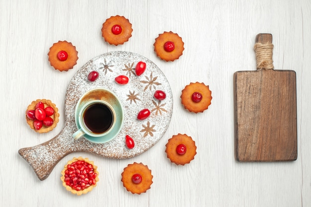 Bovenaanzicht heerlijke taarten met fruit en kopje thee op wit bureau