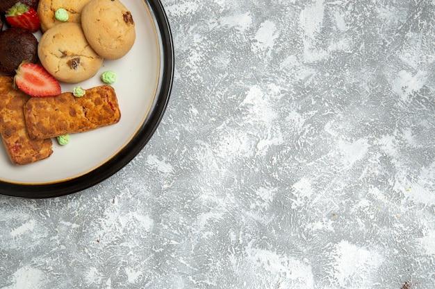 Bovenaanzicht heerlijke taarten met koekjes en aardbeien op de witte achtergrond biscuit suiker cake zoete taart thee koekjes