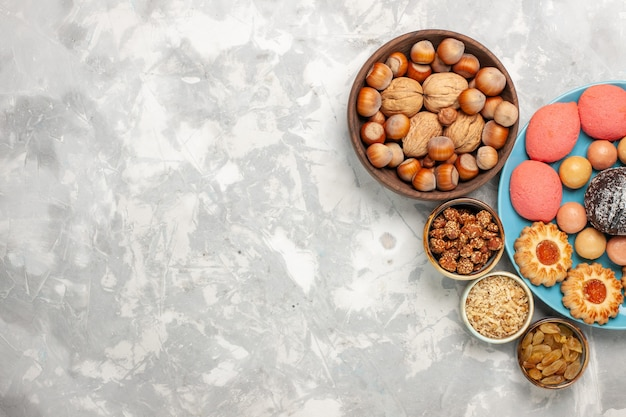Bovenaanzicht heerlijke taarten met macarons, noten en koekjes op het witte bureau