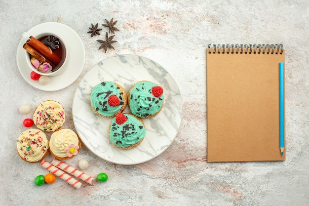 Bovenaanzicht heerlijke taarten met snoep en kopje thee op witte desk biscuit cake zoete thee dessert