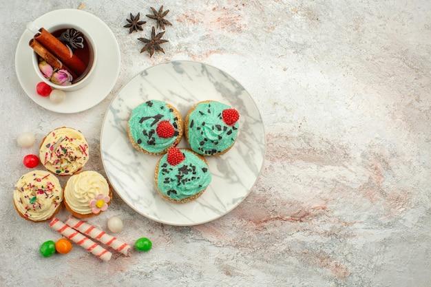 Bovenaanzicht heerlijke taarten met snoep en kopje thee op witte oppervlakte biscuit cake zoete thee dessert