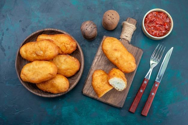 Bovenaanzicht heerlijke taarten met vlees vulling in houten plaat op de donkerblauwe achtergrond deeg taart brood broodje voedsel bakken