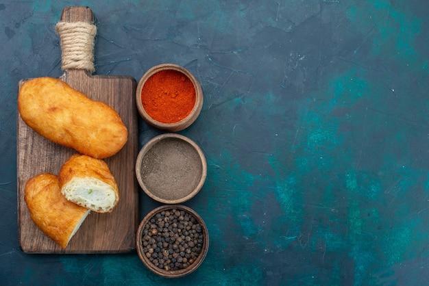 Bovenaanzicht heerlijke taarten met vleesvulling en kruiden op donkerblauwe achtergrond deeg taart brood broodje bakken