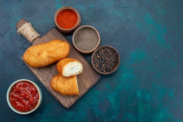 Bovenaanzicht heerlijke taarten met vleesvulling en kruiderijen op de donkerblauwe achtergrond deeg taart brood broodje voedsel bakken