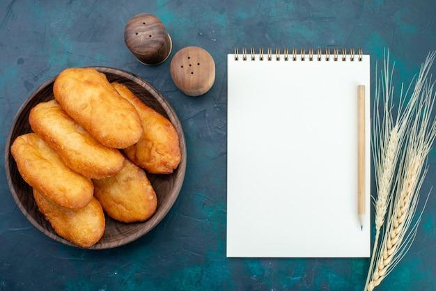 Bovenaanzicht heerlijke taarten met vleesvulling in houten plaat op donkerblauw bureau deeg taart brood broodje eten