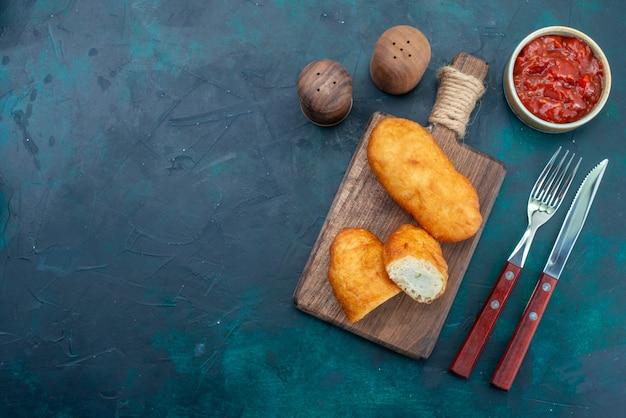 Bovenaanzicht heerlijke taarten met vleesvulling op donkerblauwe achtergrond deeg taart brood broodje voedsel bakken