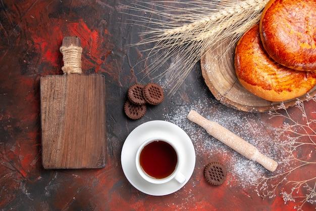 Bovenaanzicht heerlijke taarten voor kopje thee op de donkere tafel