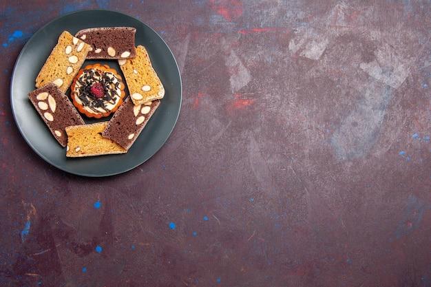 Bovenaanzicht heerlijke taartschijfjes met noten en klein koekje op donkere achtergrond biscuitkoekje zoete dessertcake