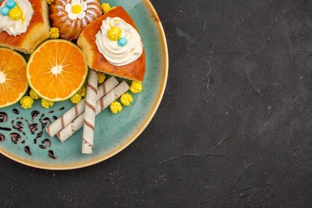 Bovenaanzicht heerlijke taartschijfjes met pijpkoekjes en gesneden mandarijnen op donkere achtergrond, fruittaarttaartkoekjes, zoete thee