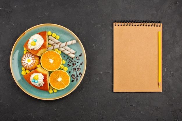 Bovenaanzicht heerlijke taartschijfjes met pijpkoekjes en gesneden mandarijnen op donkergrijze achtergrondfruit, citruscake, taartkoekje, zoete thee