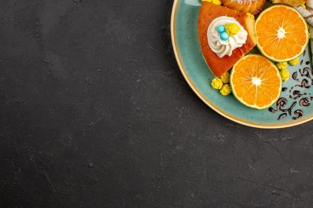 Bovenaanzicht heerlijke taartschijfjes met pijpkoekjes en gesneden mandarijnen op een donkere achtergrond, fruittaarttaartkoekje, zoete thee
