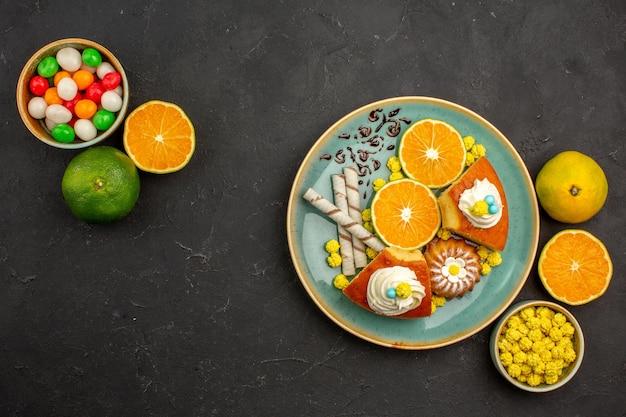 Bovenaanzicht heerlijke taartschijfjes met pijpkoekjes en vers gesneden mandarijnen op donkere bureau fruittaart taart zoete biscuit