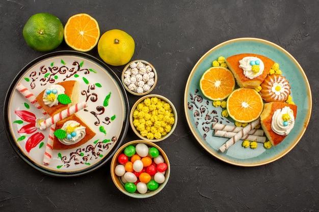 Bovenaanzicht heerlijke taartschijfjes met snoep en verse mandarijnen op donkere vloer fruitcake, zoete koekjestaart