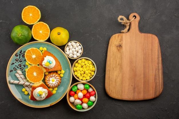 Bovenaanzicht heerlijke taartschijfjes met snoepjes en verse mandarijnen op de donkere achtergrond, fruitcake, zoete koekjestaart