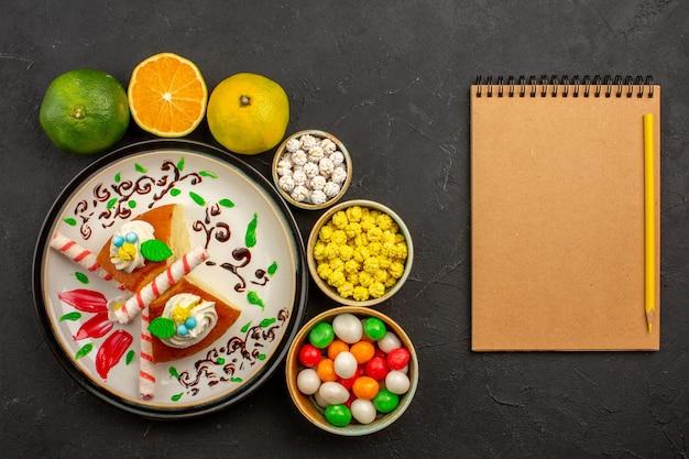 Bovenaanzicht heerlijke taartschijfjes met snoepjes en verse mandarijnen op de donkere achtergrondcake, zoete koekjestaartfruit