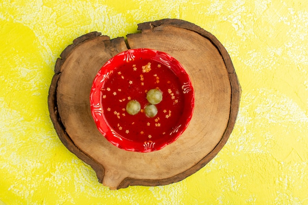 Bovenaanzicht heerlijke tomatensaus met groene druiven op geel bureau soep eten maaltijd diner