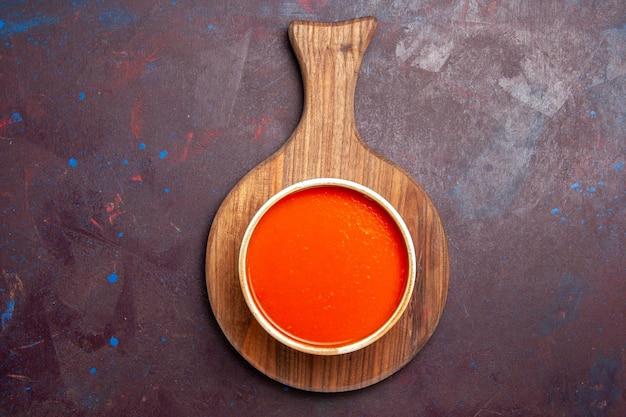 Bovenaanzicht heerlijke tomatensoep gekookt van verse rode tomaten op donkere achtergrond tomatensoep maaltijdschotel saus