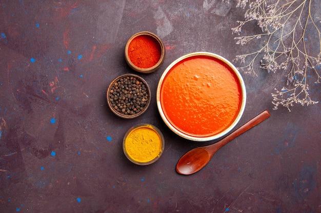 Bovenaanzicht heerlijke tomatensoep gekookt van verse tomaten met kruiden op de donkere achtergrond saus maaltijd tomatenschotel soep