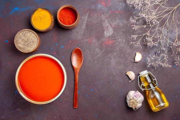Bovenaanzicht heerlijke tomatensoep gekookt van verse tomaten met kruiden op de donkere achtergrond tomatenschotel soepsaus maaltijd rood