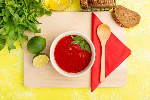 Bovenaanzicht heerlijke tomatensoep met citroen en greens op gele tafel, soep eten maaltijd diner