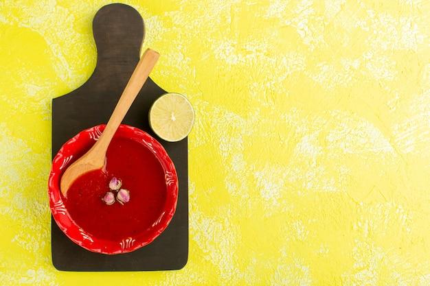 Bovenaanzicht heerlijke tomatensoep met citroen op gele tafel, soep maaltijd plantaardig voedsel