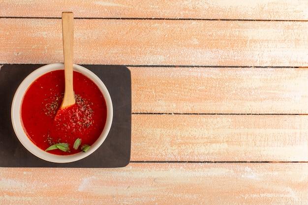 Bovenaanzicht heerlijke tomatensoep met greens binnen op tafel, soep maaltijd diner groente