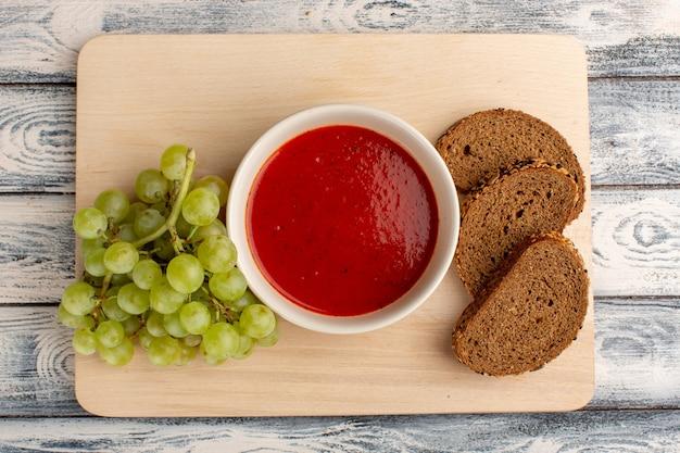 Bovenaanzicht heerlijke tomatensoep met groene druiven en donkere broodbroodjes op grijze tafel, soep eten maaltijd diner