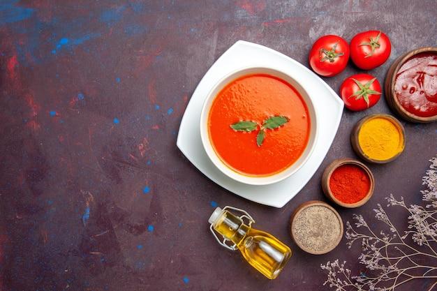 Bovenaanzicht heerlijke tomatensoep met kruiden op donkere bureauschotel saus tomatenkleur maaltijdsoep
