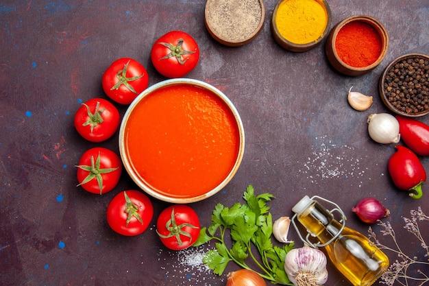 Bovenaanzicht heerlijke tomatensoep met verse tomaten en kruiden op donkere achtergrond tomatenschotel diner soepsaus maaltijd