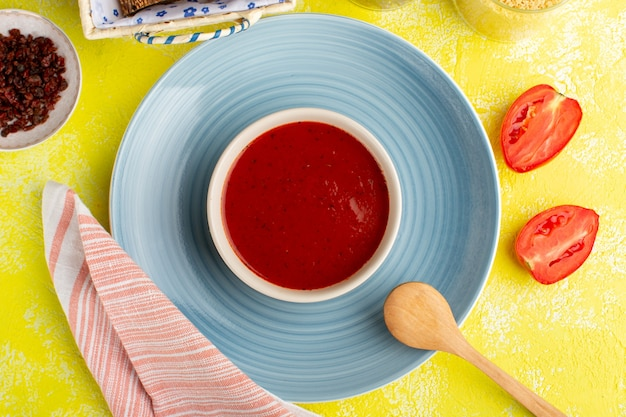 Bovenaanzicht heerlijke tomatensoep met verse tomaten op de gele tafel, kleur van de soep van het eten, diner, diner