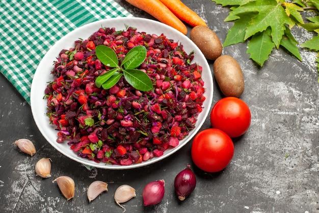 Bovenaanzicht heerlijke vinaigrette bietensalade met groenten op het grijze oppervlak