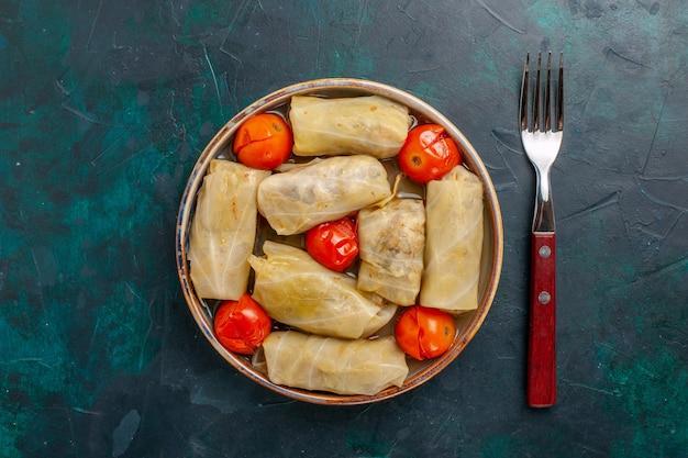 Bovenaanzicht heerlijke vleesmaaltijd gerold in kool met tomaten en vork op donkerblauw bureau vlees eten diner calorieën groente koken