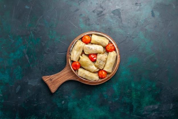Bovenaanzicht heerlijke vleesmaaltijd gerold in kool met tomaten op het donkerblauwe bureau vlees eten diner calorieën groenteschotel koken
