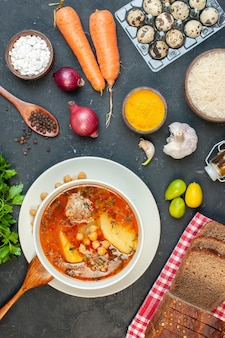 Bovenaanzicht heerlijke vleessoep bestaat uit aardappelen, bonen en vlees op donkere achtergrond