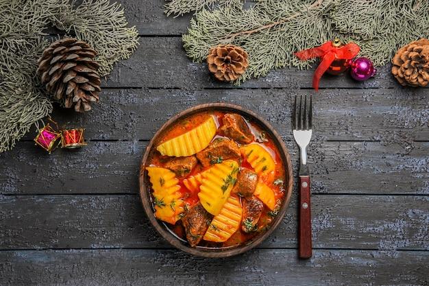 Bovenaanzicht heerlijke vleessoep met aardappelen en groenen op donkere vloer