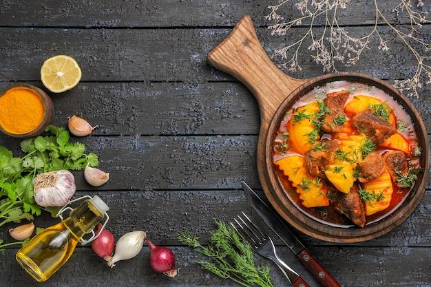 Bovenaanzicht heerlijke vleessoep met aardappelen en groenten op het donkere bureau