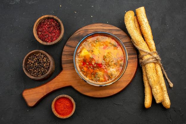 Bovenaanzicht heerlijke vleessoep met brood en kruiden op donkergrijze ruimte