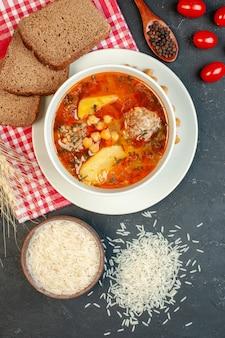 Bovenaanzicht heerlijke vleessoep met brood en tomaten op de donkere achtergrond