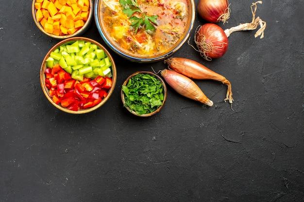 Bovenaanzicht heerlijke vleessoep met gesneden groenten op de grijze ruimte
