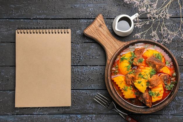 Bovenaanzicht heerlijke vleessoep met groene aardappelen op het donkere bureau