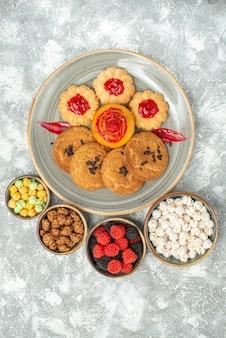 Bovenaanzicht heerlijke zandkoekjes met koekjes en snoepjes op lichte witte achtergrondkoekje, zoete suikercake, theekoekje
