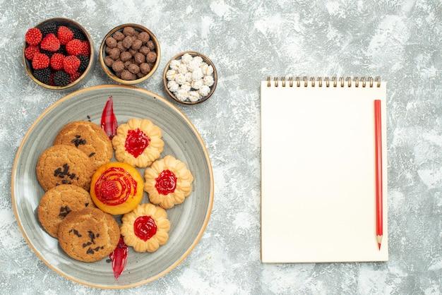 Bovenaanzicht heerlijke zandkoekjes met koekjes en snoepjes op wit bureau suikerkoekje cake koekjesthee zoet