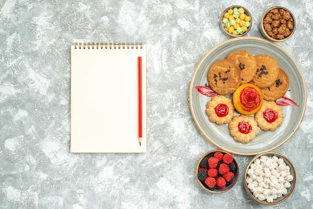 Bovenaanzicht heerlijke zandkoekjes met koekjes en snoepjes op witte achtergrond biscuit zoete cake cookie suiker thee