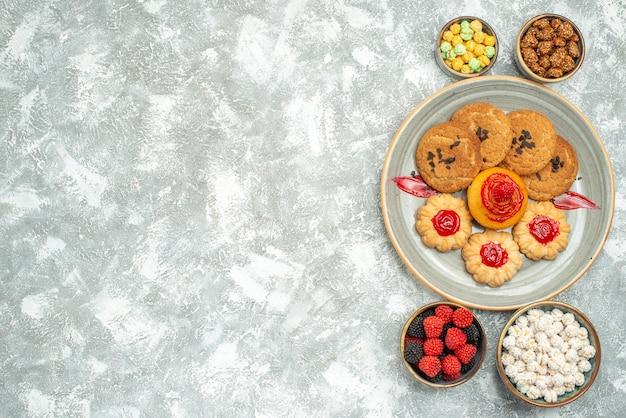 Bovenaanzicht heerlijke zandkoekjes met koekjes en snoepjes op witte achtergrond biscuit zoete cake thee cookie suiker