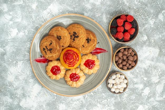 Bovenaanzicht heerlijke zandkoekjes met koekjes en snoepjes op witte achtergrond suikerkoekjes cake koekjes thee zoet